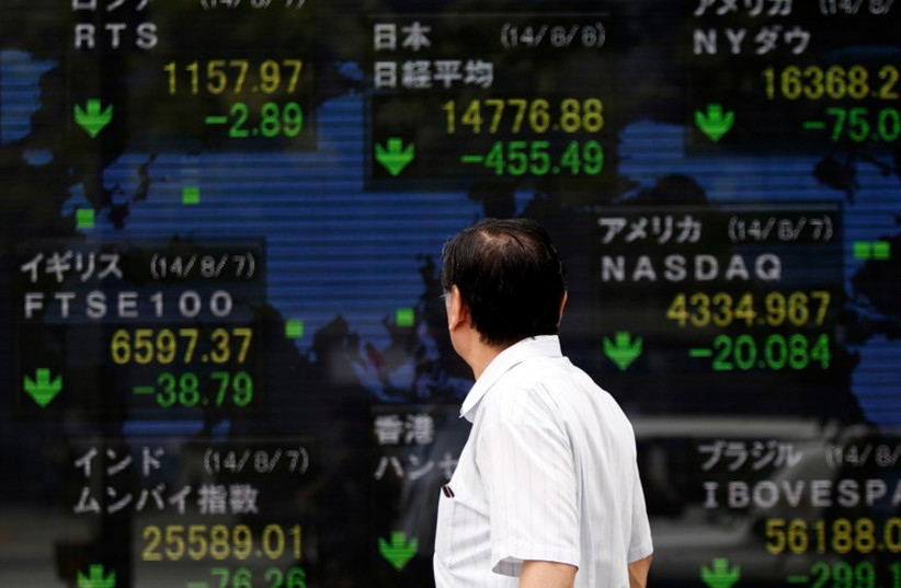 A pedestrian looks at an electronic board showing the stock market indices of various countries outside a brokerage in Tokyo. (photo credit: REUTERS)