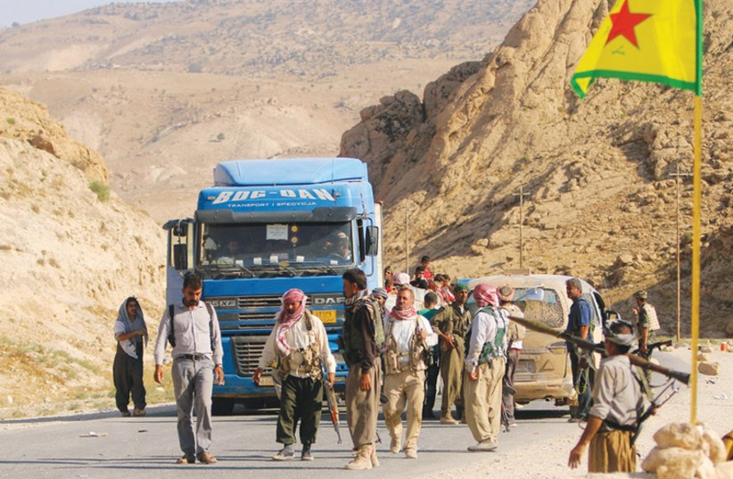 YAZIDI FIGHTERS secure a road on Mount Sinjar on Wednesday that their displaced brethren use to escape to Newrooz camp in Syria's Hasakah province. (photo credit: REUTERS)