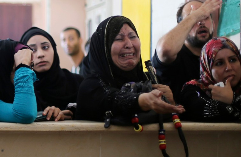 A Palestinian woman, hoping to cross into Egypt, cries as she waits with others at the Rafah crossing between Egypt and the southern Gaza Strip, August 12, 2014. (photo credit: REUTERS)