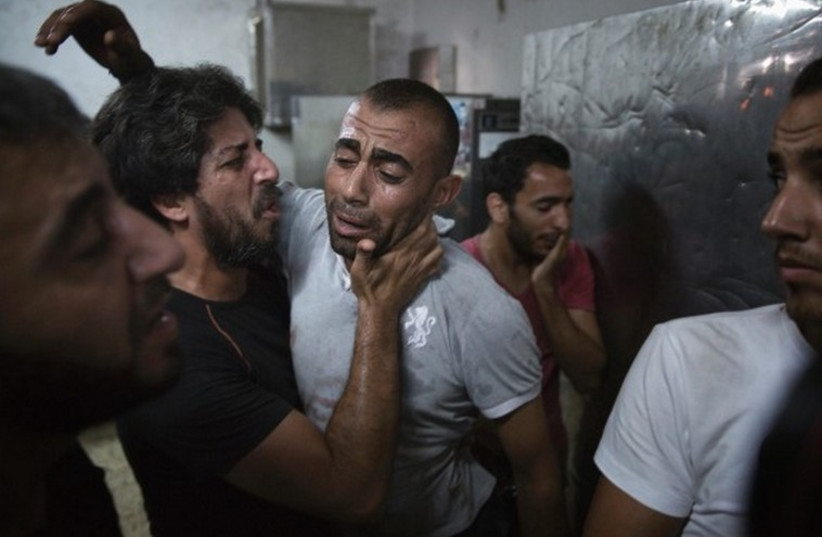 A Palestinian father reacts at the Shifa Hospital morgue after his son was killed in an explosion. (photo credit: REUTERS)