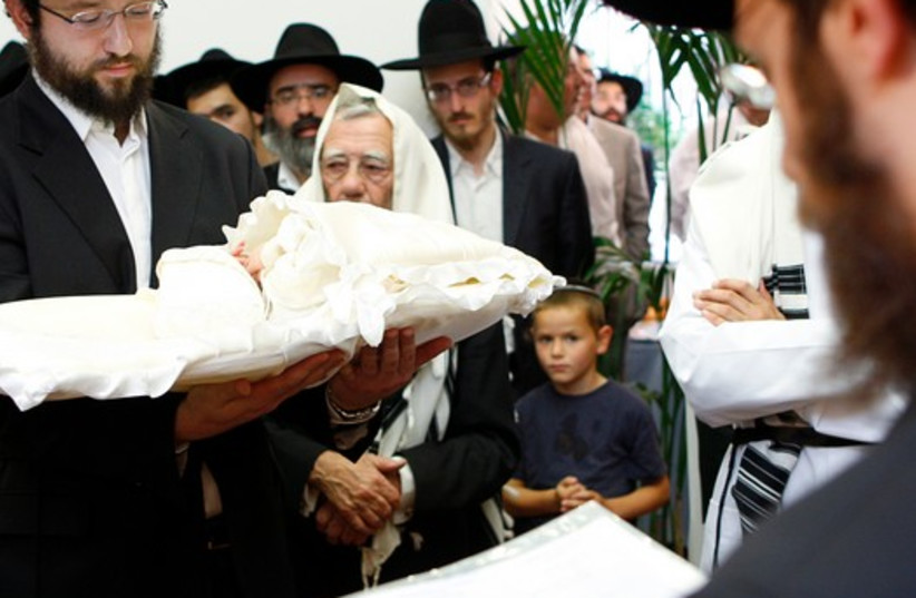 A rabbi holds an eight-day-old baby during a circumcision ceremony in Brussels, August 20, 2009. (photo credit: REUTERS)