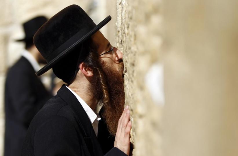 An ultra-Orthodox Jewish man kisses the Western Wall (photo credit: REUTERS)