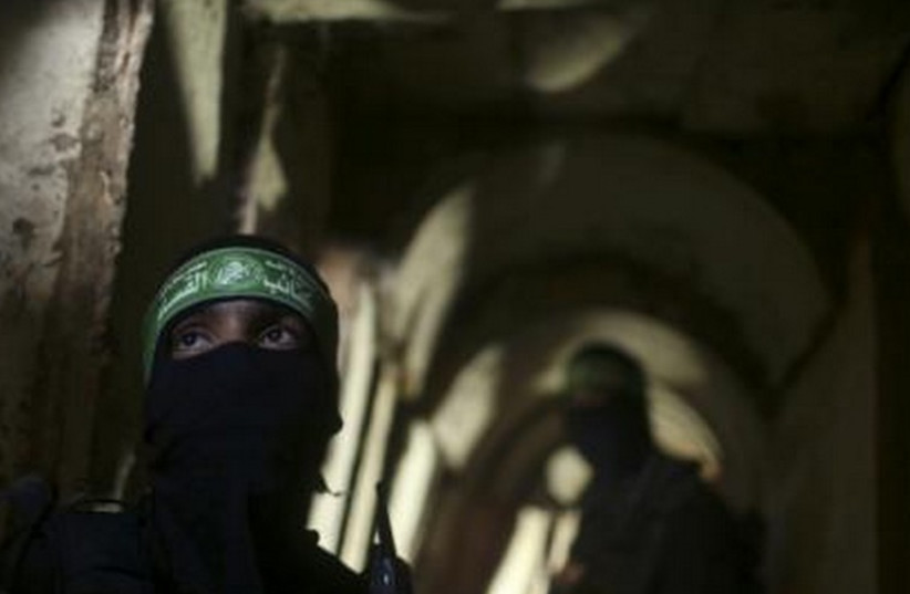 Palestinian fighters from the Izz el-Deen al-Qassam Brigades stand inside an underground tunnel in Gaza August 18 (photo credit: REUTERS)