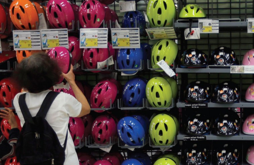 A woman shops for a bicycle helmet (photo credit: REUTERS)
