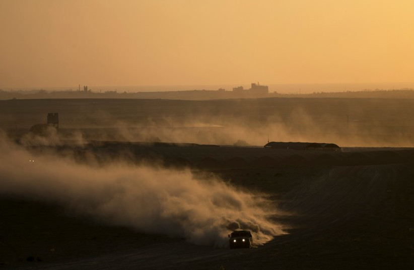 An Israeli Army jeep drives near the border with the Gaza Strip August 20 (photo credit: REUTERS)