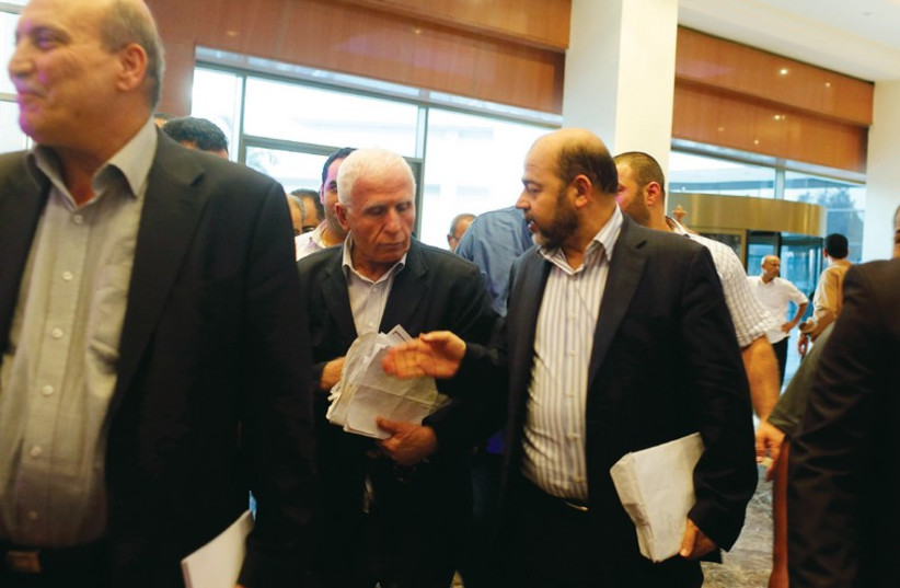 Moussa Abu Marzouk (right) talks with Fatah official and delegation leader Azzam Ahmed (photo credit: REUTERS)