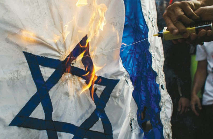 Demonstrators burn an Israeli flag in front of the Israeli Embassy in Bangkok (photo credit: REUTERS)
