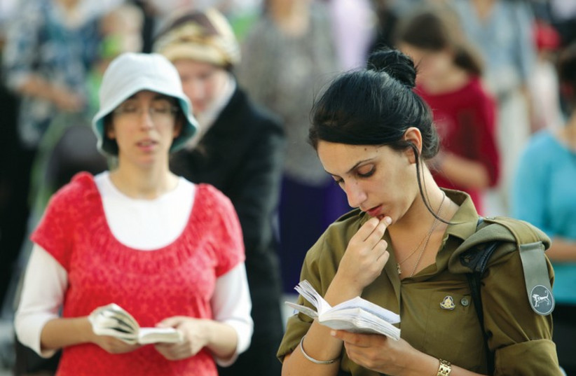A religious woman and a female soldier pray at the Western Wall. (photo credit: MARC ISRAEL SELLEM/THE JERUSALEM POST)