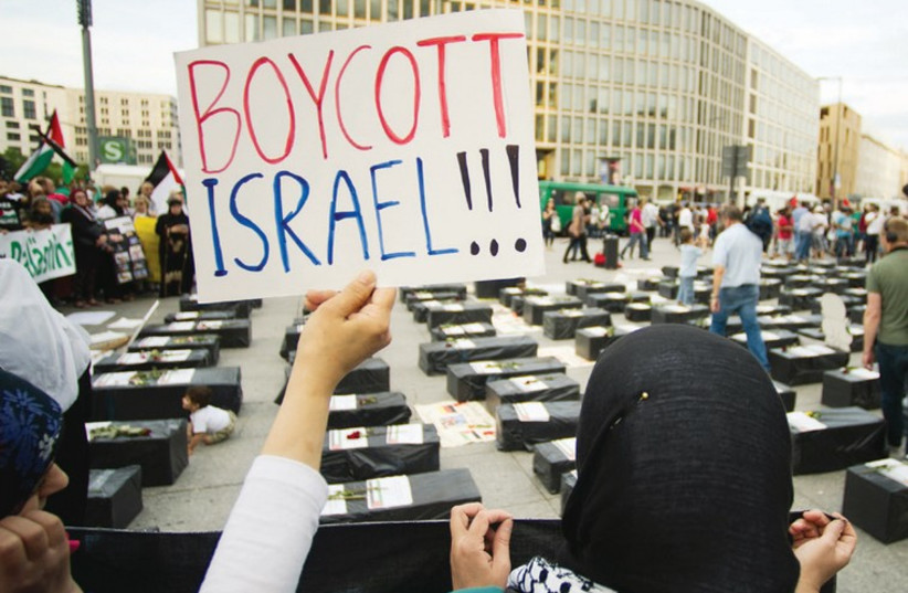 A WOMAN holds a sign during an anti-Israel protest in Berlin on August 1. (photo credit: REUTERS)
