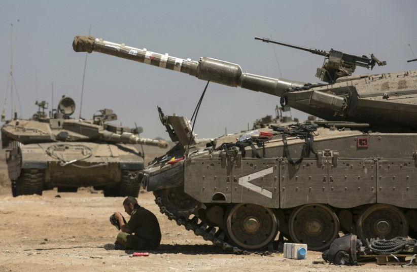 An Israeli soldier sits next to tanks at a staging area near the border with the Gaza Strip (photo credit: REUTERS)