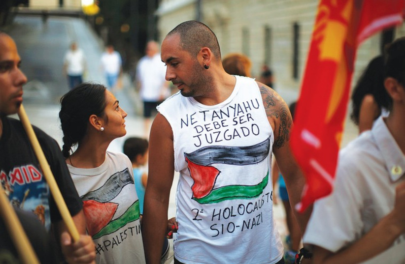 PEOPLE TAKE part in a protest against Israel in Malaga, Spain, on August 8. The words on the shirt read 'Netanyahu must be judged. Second Zionist-Nazi Holocaust.' (photo credit: REUTERS)