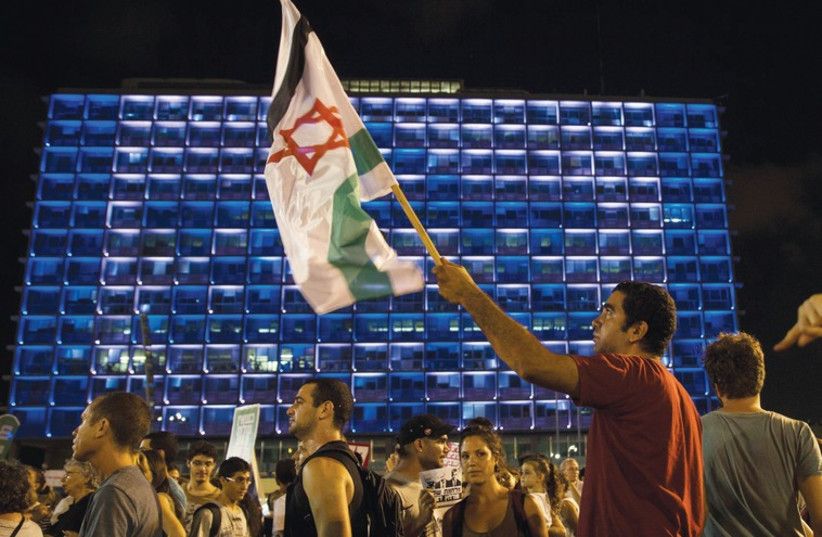 A MAN holds up a flag during a peace rally in Tel Aviv's Rabin Square  (photo credit: REUTERS)
