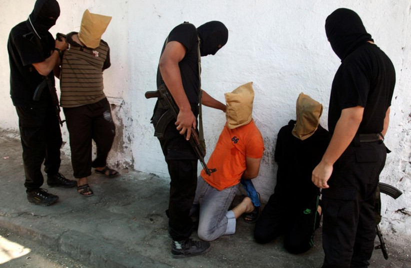 Hamas operatives prepare to execute alleged collaborators in the Gaza Strip. (photo credit: REUTERS)