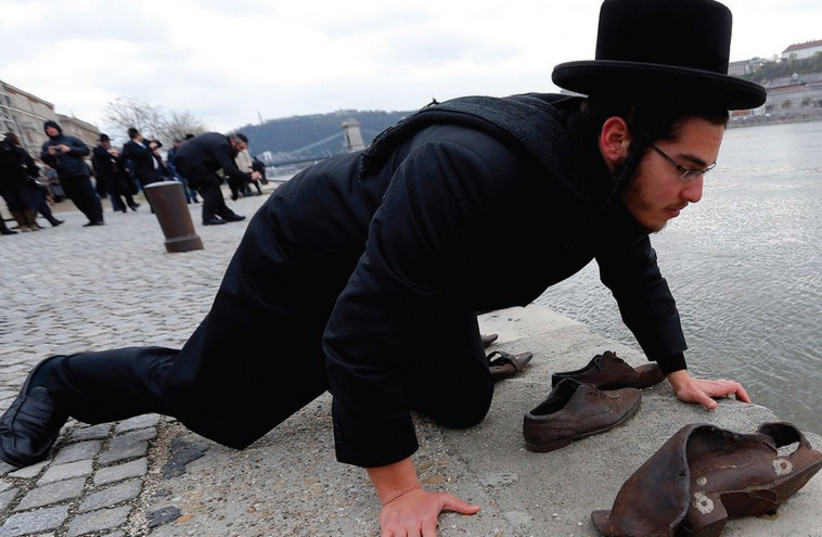An Orthodox rabbi says a prayer at a Holocaust memorial in Budapest. (photo credit: REUTERS)