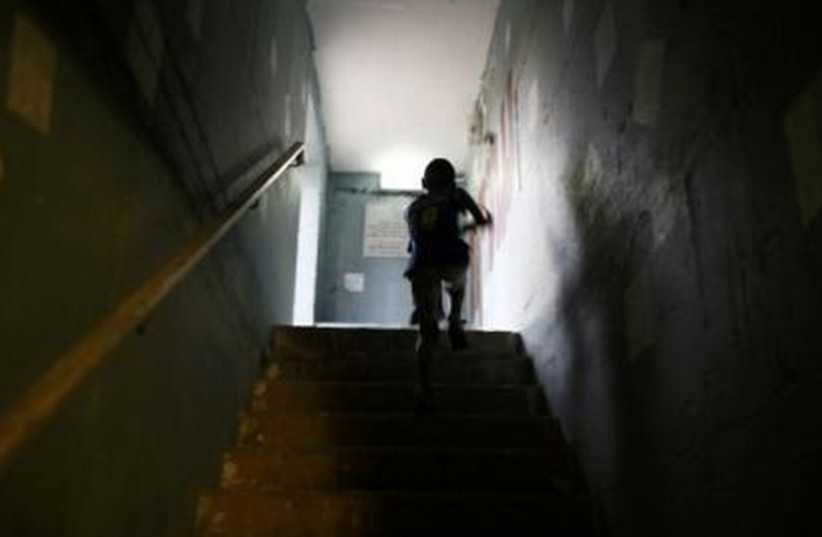 An Israeli boy runs up the stairs in a public bomb shelter. (photo credit: REUTERS)