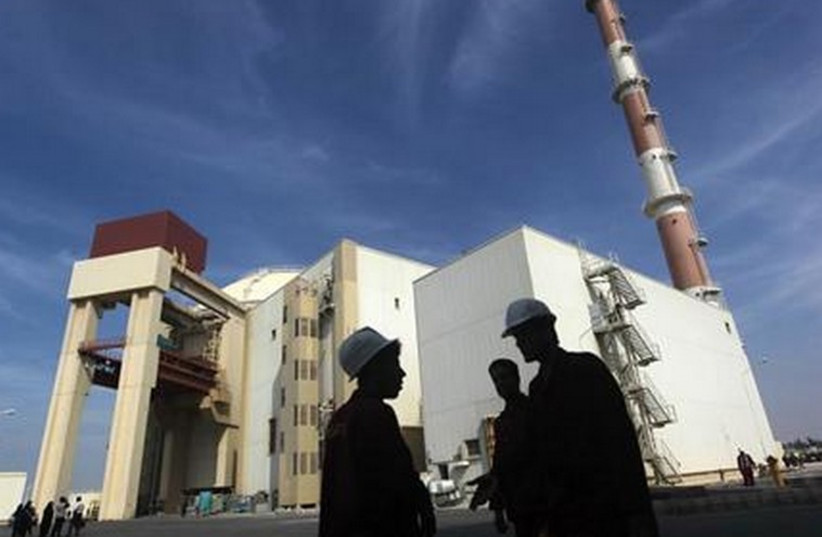 Iranian workers stand in front of the Bushehr nuclear power plant. (photo credit: REUTERS)