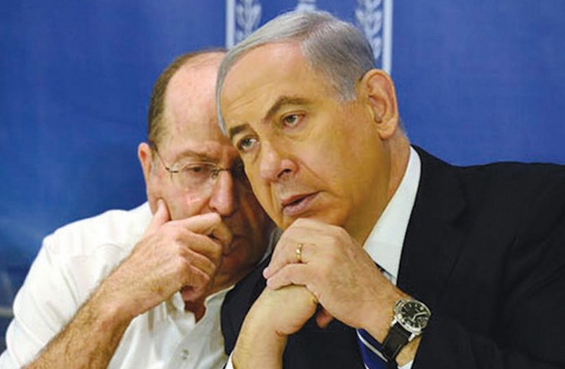 Prime Minister Binyamin Netanyahu, right, confers with Defense Minister Moshe Ya'alon. (photo credit: HAIM ZACH/GPO)