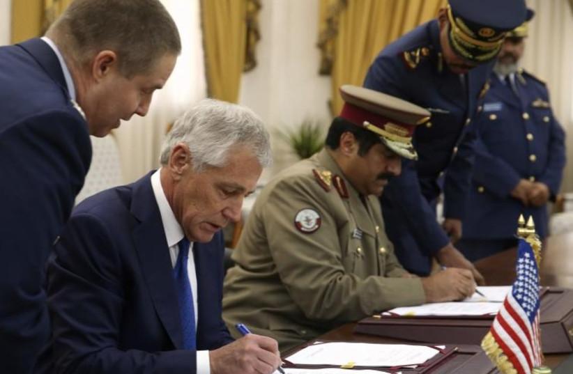 US Secretary of Defense Chuck Hagel, left, and Qatari Defense Minister Hamad bin Ali al-Attiyah sign a Defense Cooperation Agreement in Doha Dec. 10, 2013. (photo credit: REUTERS)
