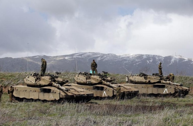 IDF soldiers stand atop tanks in the Golan Heights near Israel's border with Syria. (photo credit: REUTERS)