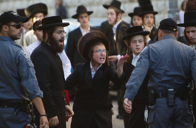 Haredim take part in a protest in Mea She'arim against the municipality opening a nearby road on Shabbat. (photo credit: REUTERS/BAZ RATNER)