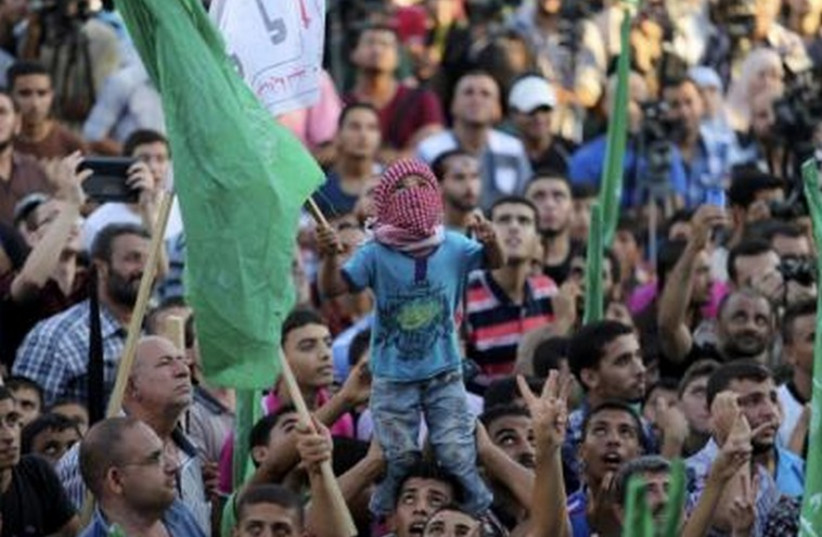 Hamas supporters celebrate with people what they said was a victory over Israel in Gaza City, August 27 (photo credit: REUTERS)