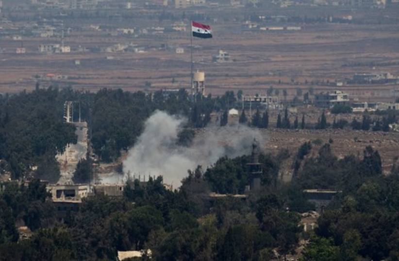 Smoke rises following an explosion on the Syrian side near the Quneitra border crossing between the Golan Heights and Syria, August 29, 2014. (photo credit: REUTERS)