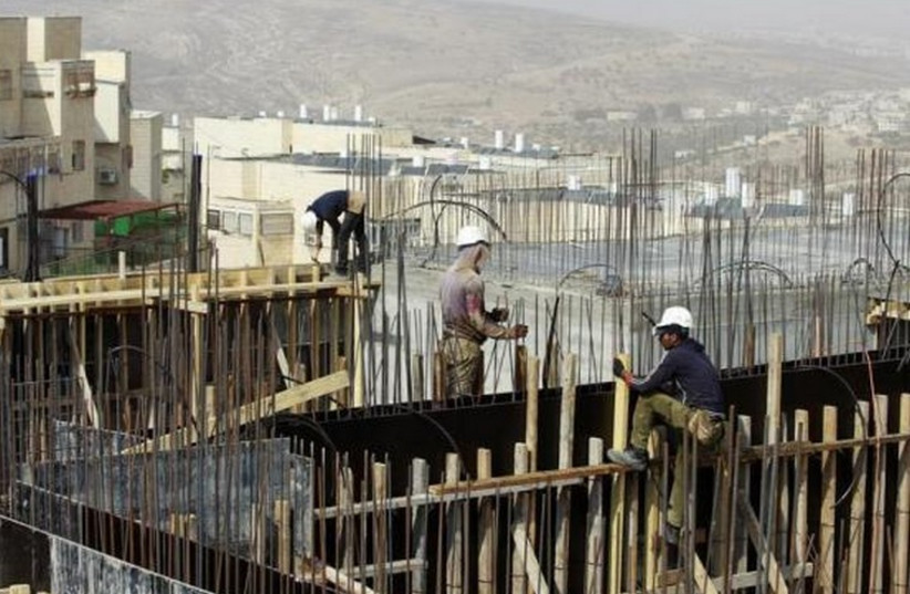Palestinian laborers work on a construction site in a religious Jewish settlement in the West Bank. [File] (photo credit: REUTERS)