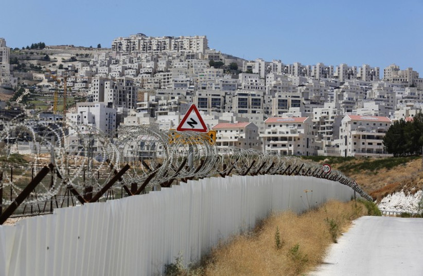 A section of the controversial Israeli barrier is seen close to a Jewish settlement near Jerusalem  (photo credit: REUTERS)