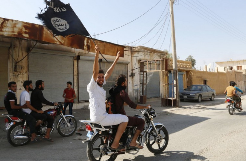Syrian waves an Islamist flag in celebration after Islamic State militants took over Tabqa air base (photo credit: REUTERS)