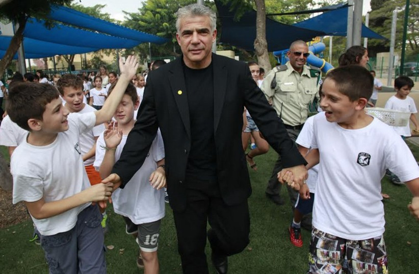 Finance Minister Yair Lapid with first-graders in Sha'ar Hanegev. (photo credit: RAANAN COHEN)