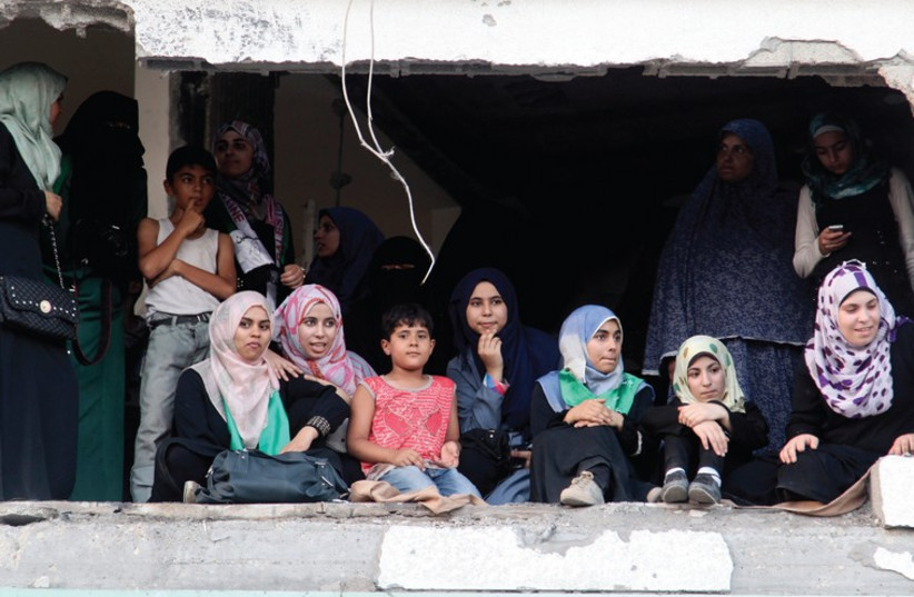 PALESTINIANS SIT in a damaged house as they watch a parade celebrating Hamas's 'victory' over Israel, in the Shejaia neighborhood, Gaza (photo credit: REUTERS)
