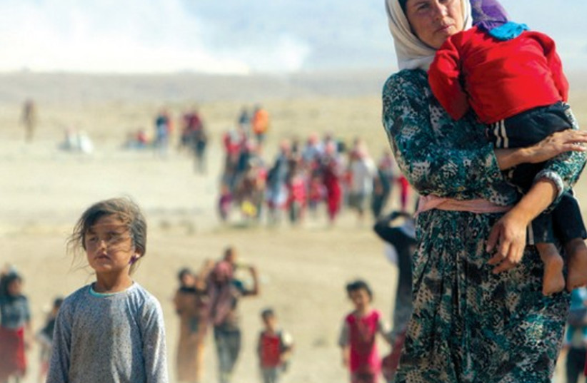 Yazidi refugees flee for their lives from Islamic State forces near the Syrian border, August 11. (photo credit: RODI SAID / REUTERS)