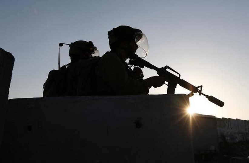 Soldiers keep guard at checkpoint near Qalandia  (photo credit: REUTERS)