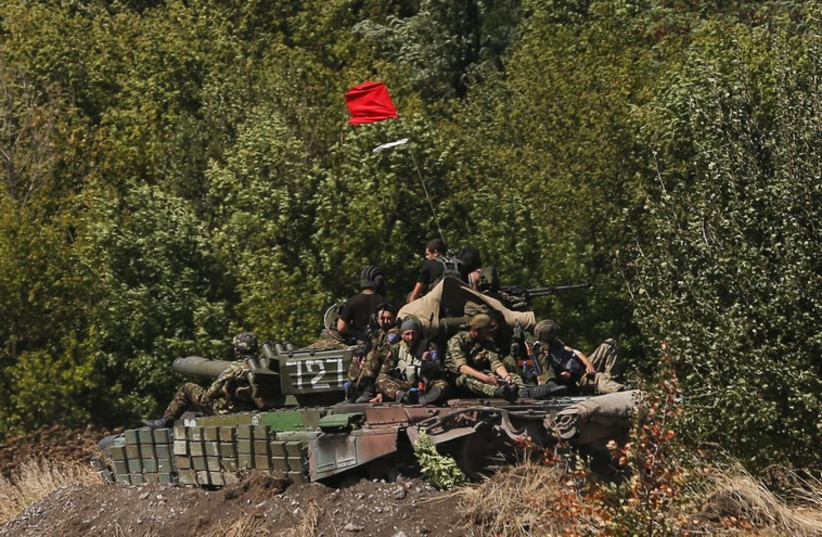 Pro-Russian separatists sit on a tank at a position near Donetsk, eastern Ukraine, September 2 (photo credit: REUTERS)