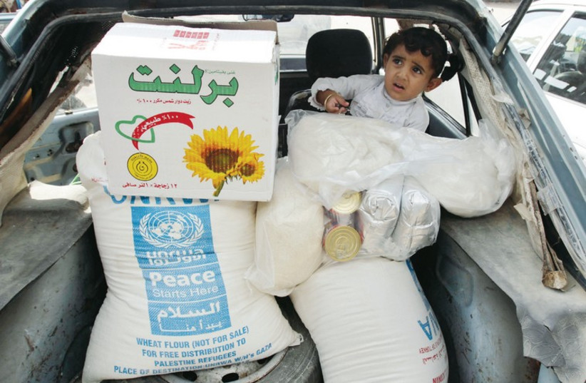A palestinian child sits in a car after her family received food supplies from the UNRWA headquarters in Rafah in the southern Gaza Strip, in this photo from November, 2012 (photo credit: REUTERS)