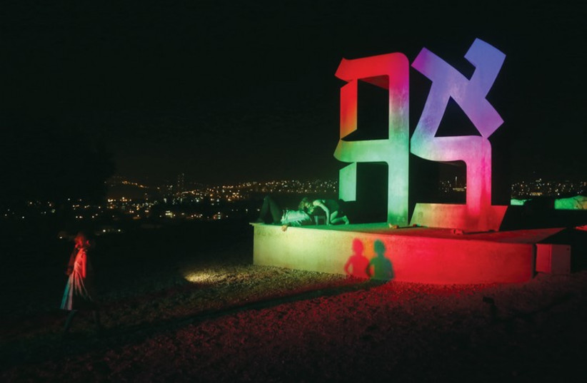 A couple kisses under the 'Ahava' (love) sculpture at Jerusalem's Israel Museum. (photo credit: MARC ISRAEL SELLEM/THE JERUSALEM POST)