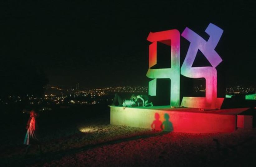 A couple kisses under the 'Ahava' (love) sculpture at Jerusalem's Israel Museum. (photo credit: MARC ISRAEL SELLEM/THE JERUSALEM POST)