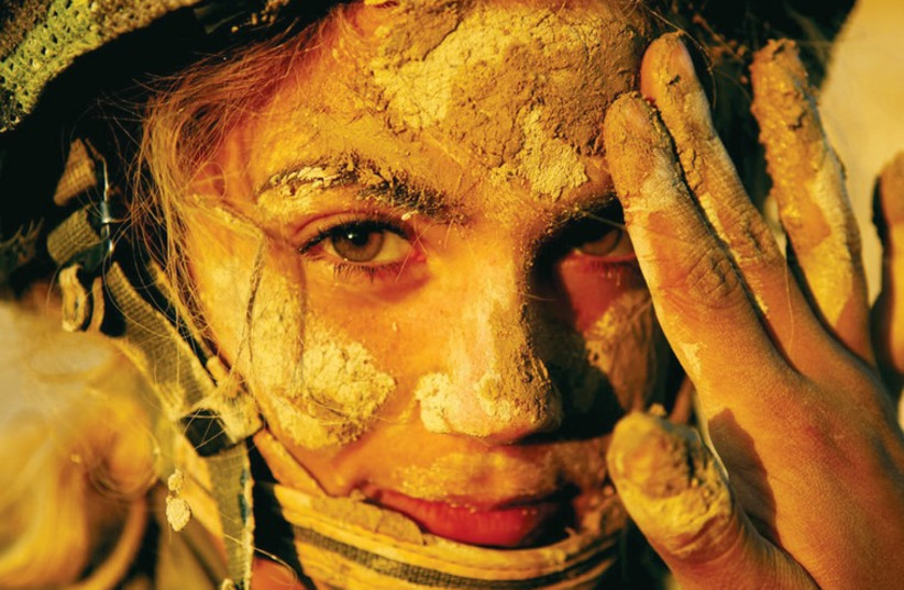 A female soldier has mud applied to her face for camouflage in this photo from an IDF Instructors course in 2006. (photo credit: IDF FLICKR)