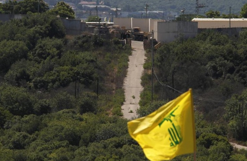 Israeli soldiers and trucks are seen from southern Lebanon, as a Hezbollah flag flutters. (photo credit: REUTERS)