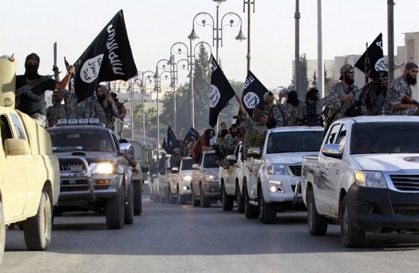 Militant Islamist fighters parade on military vehicles along the streets of Raqqa after capturing territory in neighbouring Iraq (photo credit: REUTERS/KNESSET)