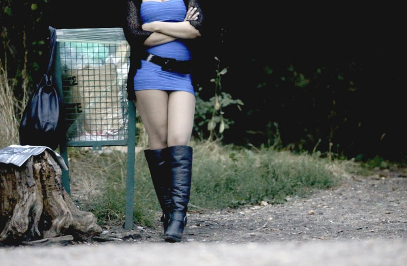 A prostitute waits for customers along a road. (photo credit: REUTERS)