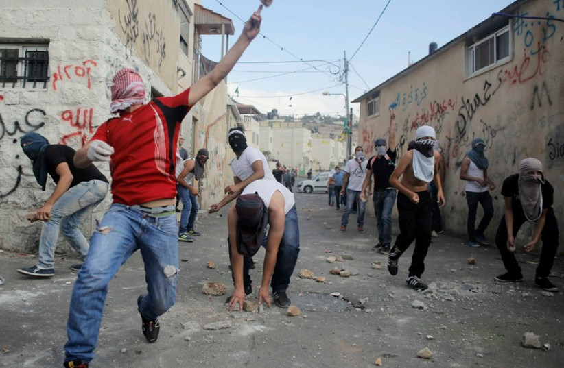 Palestinians hurl stones during clashes with Israeli police in east Jerusalem's Wadi al-Joz neighbourhood [File] (photo credit: REUTERS)