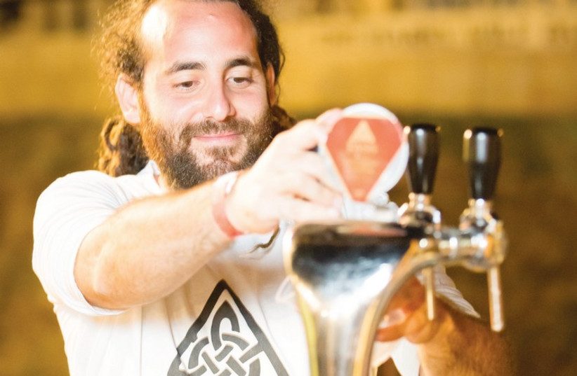 Or Fass, co-owner of the microbrewery Fass Beers on the Golan, pours a pale ale at the Jerusalem Beer Festival. (photo credit: IGOR FARBEROV)