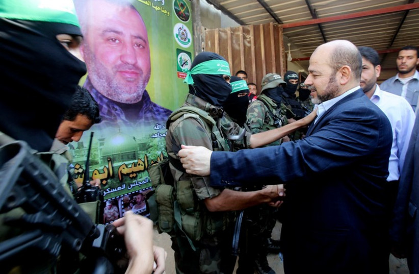 Hamas political leader Musa Abu Marzouk (R) shakes hands with a Hamas militant as he visits the mourning tent of senior Hamas commander Mohammed Abu Shammala (seen in posters). (photo credit: REUTERS)