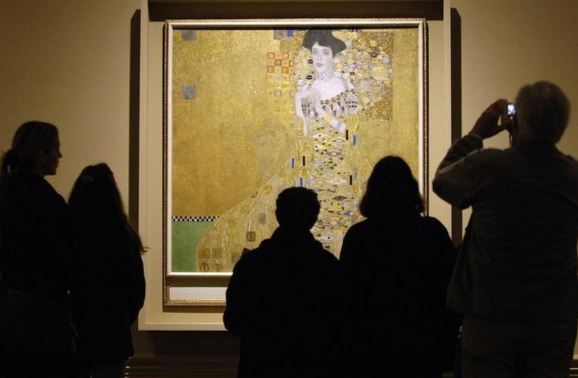 """Museum visitors study """"Adele Bloch-Bauer I,"""" a 1907 painting by Austrian artist Gustav Klimt at a special exhibition of Klimt paintings looted by the Nazis during World War II.  (photo credit: REUTERS)"""