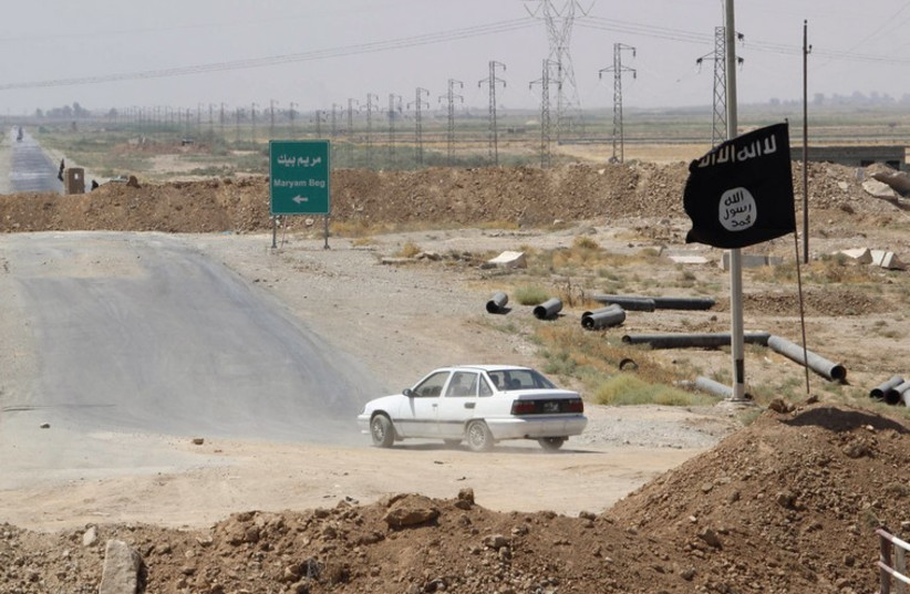 A car drives near a flag belonging to Islamic State militants at the end of a bridge in southern Kirkuk (photo credit: REUTERS)
