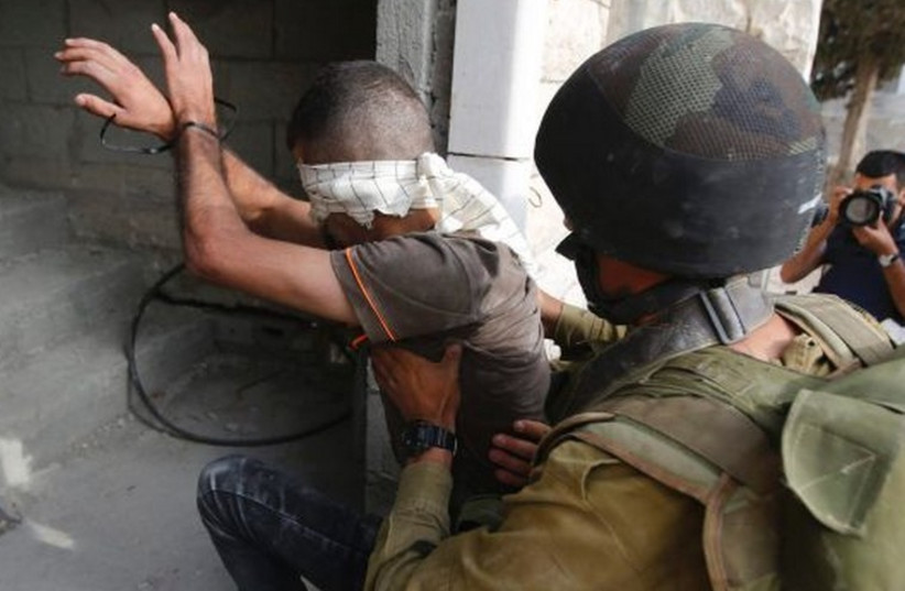 An IDF soldier detains a Palestinian near Hebron. (photo credit: REUTERS)