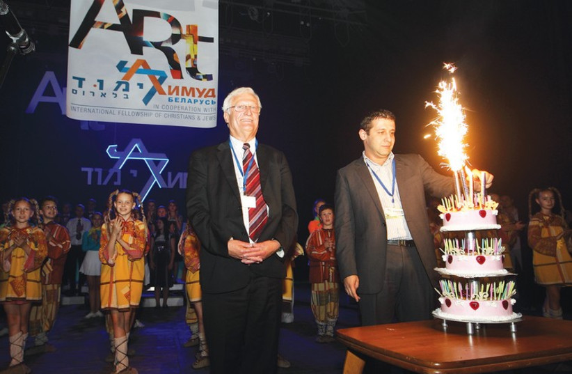 THE JOINT DISTRIBUTION COMMITTEE'S new Belarus country director Alex Kushnir lights 100-year-old philanthropist Ralph Goldman's birthday cake in Vitebsk with Limmud founder Chaim Chesler and event performers looking on. (photo credit: YOSSI ALONI)