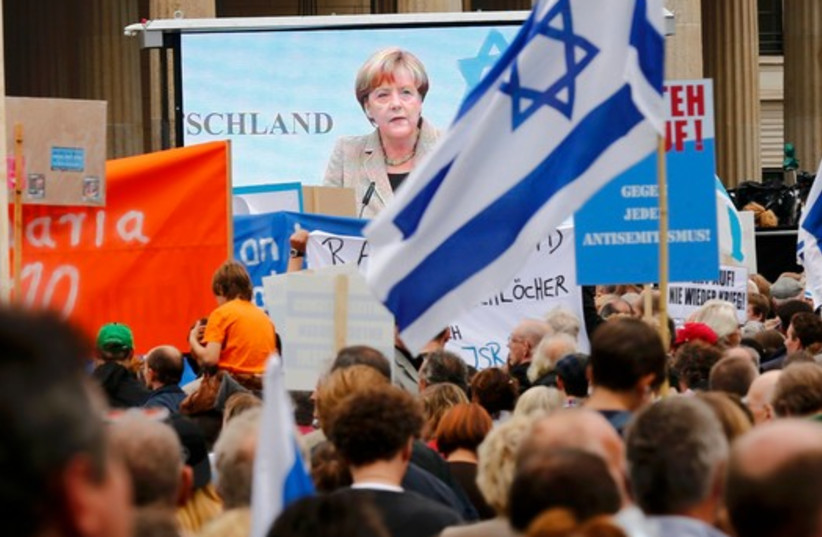 German Chancellor Angela Merkel (C) appears on a large screen as she makes an address during an anti-Semitism in Berlin. (photo credit: REUTERS)