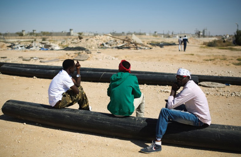 AFRICAN MIGRANTS sit on pipes outside Holot, a detention centre in Israel's southern Negev desert. (photo credit: REUTERS)